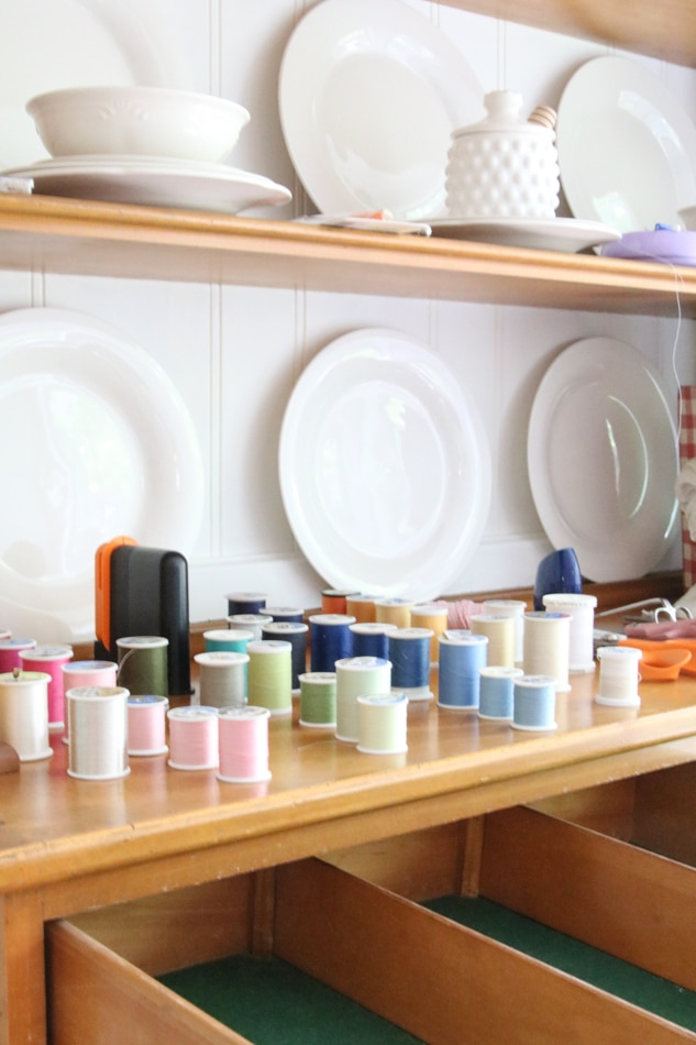 how to organize sewing supplies on a budget by placing all the spools of thread on the counter first.