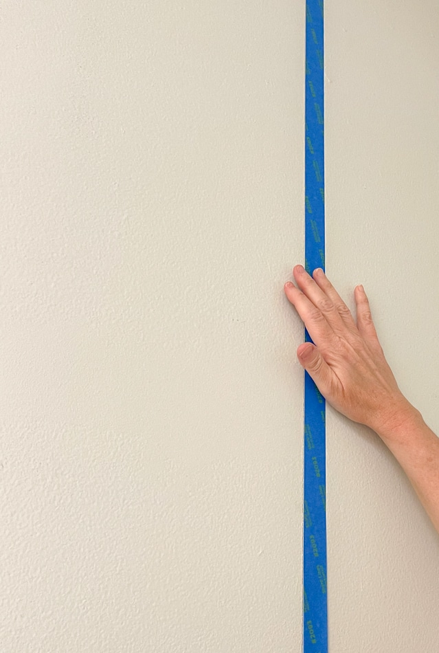 Placing painters tape on the wall to paint the background of this DIY mud room storage unit.